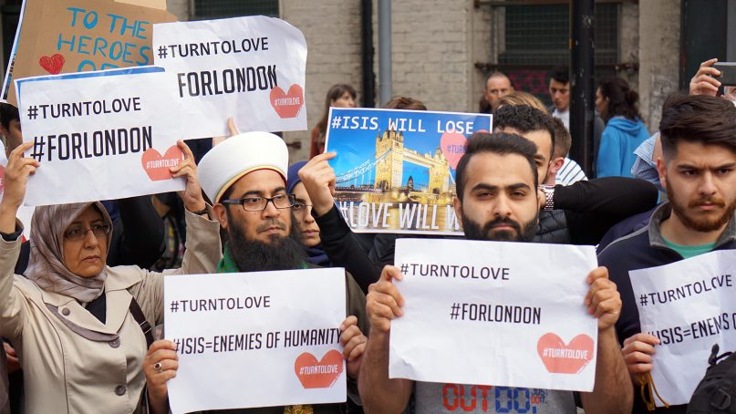Muslims hold signs saying