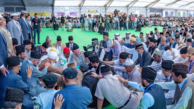Ahmadi Muslim men participate in the initiation ceremony, forming a continuous link to the caliph, left center, at the Jalsa Salana in Alton, England, on Aug. 5, 2018. Photo courtesy of Ahmadiyya Muslim Community