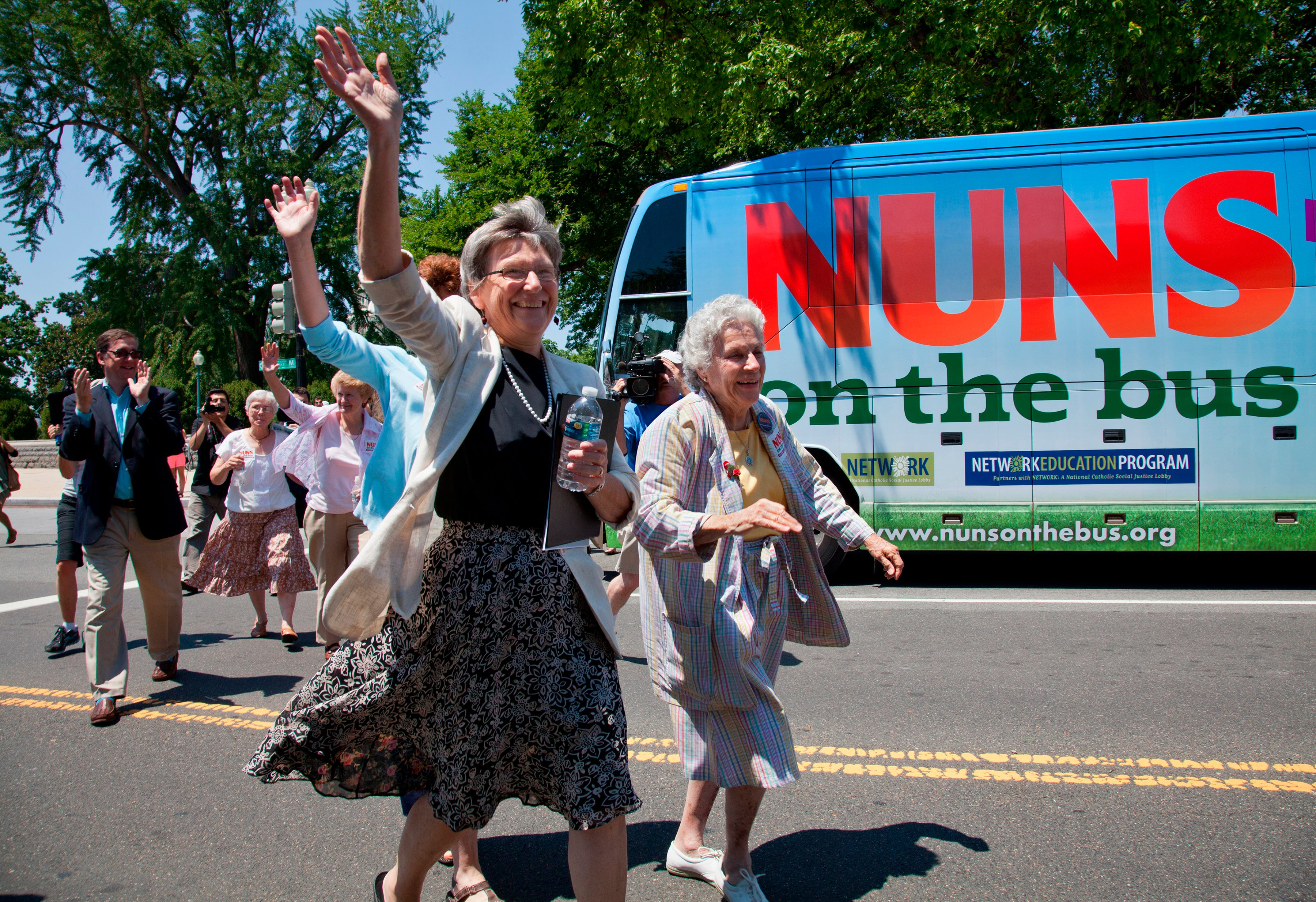 """Sister Simone Campbell, left, and Sister Diane Donoghue, right, lead the way as the the """"Nuns on the Bus"""" arrive on Capitol Hill in Washington, on July 2, 2012, after a nine-state tour to bring stories of hardship to Congress. Sister Simone Campbell is executive director of Network, a liberal Catholic social justice lobby in Washington. (AP Photo/J. Scott Applewhite)"""