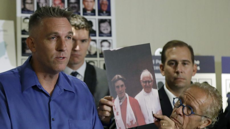 Tom Emens, left, who was sexually abused by a priest, speaks on his experience next to attorney Jeff Anderson on Oct. 2, 2018, in Los Angeles. Anderson is holding a photograph of Emens as a boy next to the priest who abused him, Monsignor Thomas Joseph Mohan. Survivors of clergy sexual assault announced the filing of a nuisance lawsuit against California Roman Catholic bishops for covering up abuse. (AP Photo/Marcio Jose Sanchez)