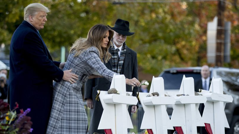 First lady Melania Trump, accompanied by President Trump and Tree of Life Rabbi Jeffrey Myers, right, puts down a white flower at a memorial for those killed at the Tree of Life Synagogue in Pittsburgh, Tuesday, Oct. 30, 2018. (AP Photo/Andrew Harnik)