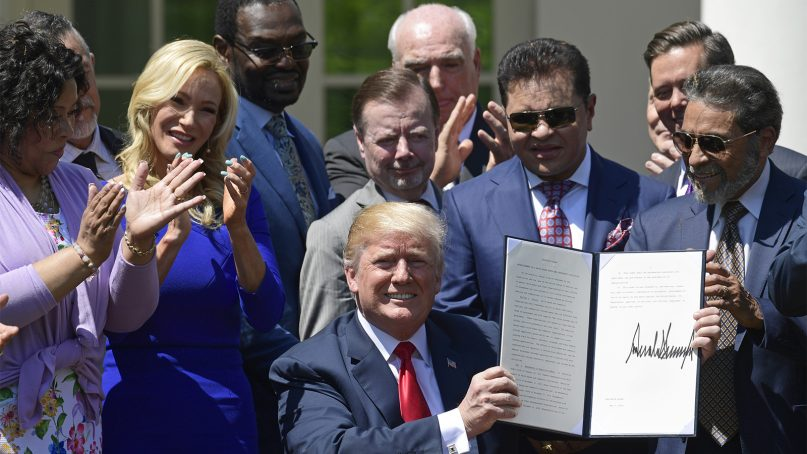President Trump, largely surrounded by evangelical leaders, holds up an executive order that he signed during a National Day of Prayer event in the Rose Garden of the White House in Washington, D.C., on May 3, 2018. (AP Photo/Susan Walsh)