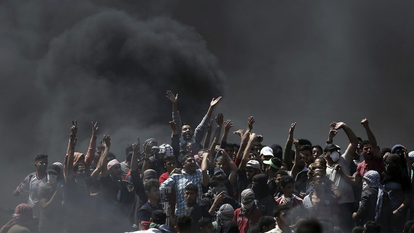Palestinian protesters chant slogans as they burn tires during a protest on the Gaza Strip's border with Israel on May 14, 2018. Thousands of Palestinians protested near Gaza's border with Israel, as Israel prepared for the festive inauguration of a new U.S. Embassy in contested Jerusalem. (AP Photo/Khalil Hamra)