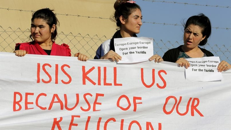 Yazidi refugee women hold a banner as they wait for the arrival of United Nations High Commissioner for Refugees Special Envoy Angelina Jolie at a Syrian and Iraqi refugee camp in the southern Turkish town of Midyat in Mardin province, Turkey, on June 20, 2015. Photo courtesy of REUTERS/Umit Bektas