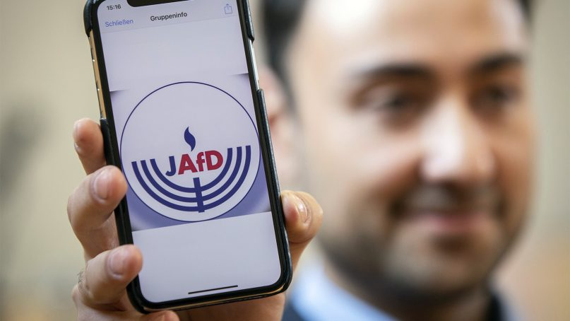 Leon Hakobian presents a temporary draft of a logo of the 'National Association of Jews in the Alternative Fuer Deutschland' group prior to a press conference in Wiesbaden, Germany, on Oct. 7, 2018. The far-right Alternative for Germany party announced it will create a Jewish section within the party, drawing widespread criticism by Jewish groups across the country. (Frank Rumpenhorst/dpa via AP)