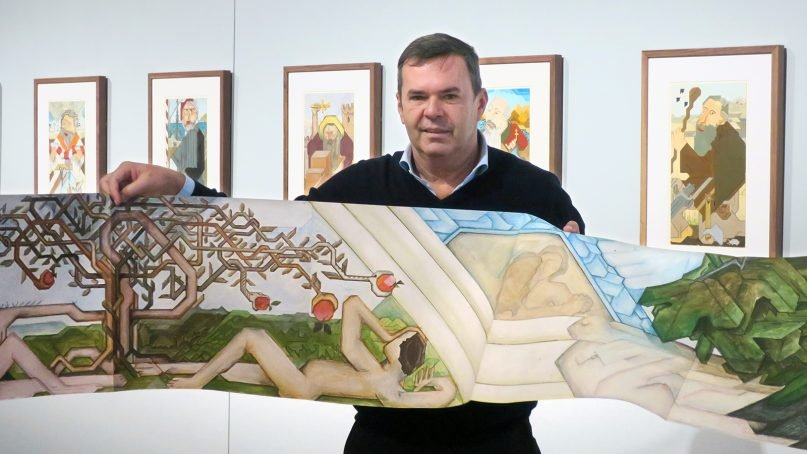 Martin Wiedmann holds part of a printed copy of his father's work, which is open to the Genesis creation narrative, at the Museum of the Bible in Washington. Behind him are paintings from a different series by his father, Willy Wiedmann, on the Twelve Apostles. RNS photo by Menachem Wecker