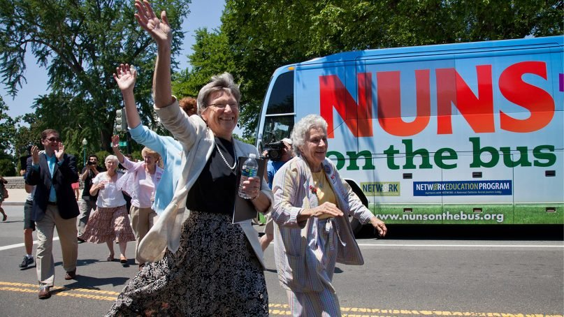 """FILE - Sister Simone Campbell, left, and Sister Diane Donoghue, right, lead the way as the """"Nuns on the Bus"""" arrive on Capitol Hill in Washington, D.C., on July 2, 2012. Campbell has recently spoken, advocating for the counting of every vote this election. (AP Photo/J. Scott Applewhite)"""