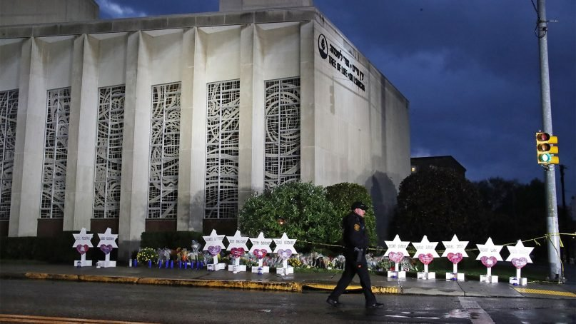A Pittsburgh police officer patrols around the Tree of Life Synagogue and a memorial of flowers and Stars of David in Pittsburgh on Oct. 28, 2018, in remembrance of those killed and injured when a shooter opened fire during services at the synagogue. (AP Photo/Gene J. Puskar)