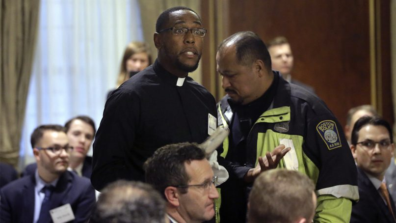 The Rev. Darrell Hamilton, center left, a pastor at First Baptist Church in Jamaica Plain, Mass., is escorted away by a Boston police officer after interrupting remarks by Attorney General Jeff Sessions, not shown, at a luncheon organized by the Boston Lawyers Chapter of the Federalist Society, on Oct. 29, 2018, in Boston. Sessions spoke about religious liberty during his remarks. (AP Photo/Steven Senne)