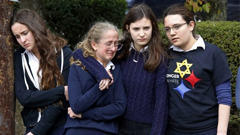 Students from the Yeshiva School in the Squirrel Hill neighborhood of Pittsburgh pay their respects as the funeral procession for Dr. Jerry Rabinowitz passes their school en route to Homewood Cemetery after a funeral service at the Jewish Community Center on Oct. 30, 2018. Rabinowitz was one of 11 people killed while worshipping at the Tree of Life synagogue on Oct. 27, 2018. (AP Photo/Gene J. Puskar)