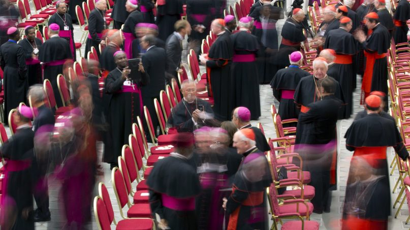 In this photo taken with a slow shutter speed, cardinals and bishops arrive in the Paul VI Hall at the Vatican for a meeting marking the 50th anniversary of the creation of the Synod of Bishops, on Oct. 17, 2015. (AP Photo/Alessandra Tarantino)