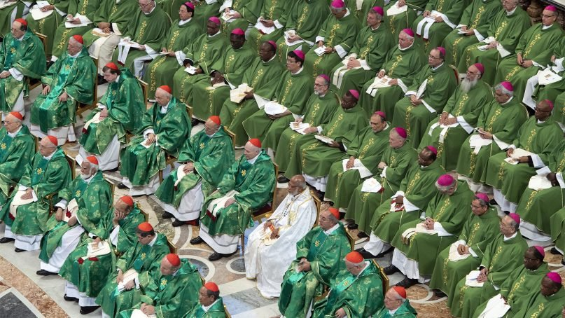 Cardinals, wearing red caps in the two front rows from left, and bishops attend a Mass celebrated by Pope Francis for the closing of the month-long synod of bishops, inside St. Peter's Basilica, at the Vatican, on Oct. 28, 2018. (Claudio Peri/Pool Photo via AP)