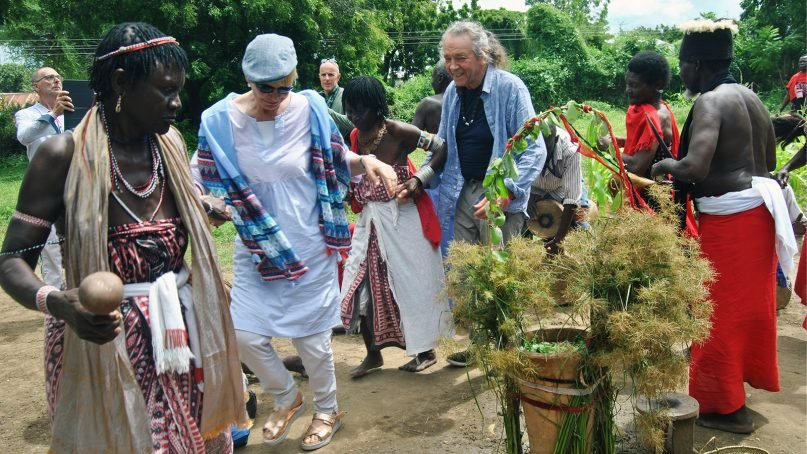 Witch doctors take Italian tourist Grazie Jei, second left, and others through a traditional dance around a container of an herb-infused potion as part of treatments that some tourists sought out in Mombasa, Kenya, on July 7, 2018. RNS photo by Tonny Onyulo
