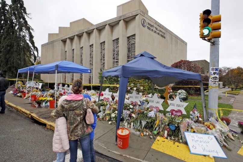 A woman and her children pause Nov. 3, 2018, to take in a makeshift memorial outside the Tree of Life synagogue honoring the 11 people killed Oct. 27, 2018, while worshipping in the Squirrel Hill neighborhood of Pittsburgh. (AP Photo/Gene J. Puskar)
