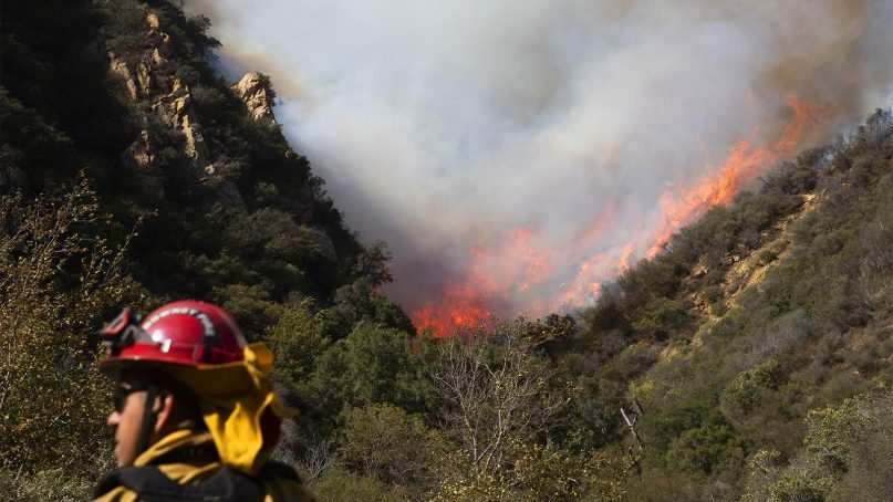 A firefighter monitors a wildfire burning along a hillside on Nov. 11, 2018, in Malibu, Calif. (AP Photo/Jae C. Hong)