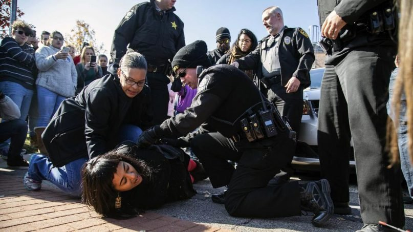 A demonstrating church member is arrested after Samuel Oliver-Bruno, 47, an undocumented Mexican national, was arrested after arriving at an appointment with immigration officials, in Morrisville, N.C., on Nov. 23, 2018. He had been living in CityWell United Methodist Church in Durham since late 2017 to avoid the reach of immigration officers, who generally avoid making arrests at churches.(AP Photo/Travis Long)
