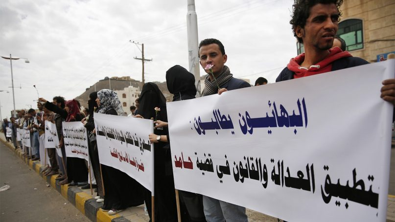 Members of the Baha'i Faith protest outside a state security court during a hearing in the case of a fellow Baha'i man, Hamid bin Haydara, suspected of contacts with Israel and charged with seeking to establish a base for the community in Yemen, in Sanaa, Yemen, on April 3, 2016. Arabic writing on the poster at right, referring to the defendant, reads,