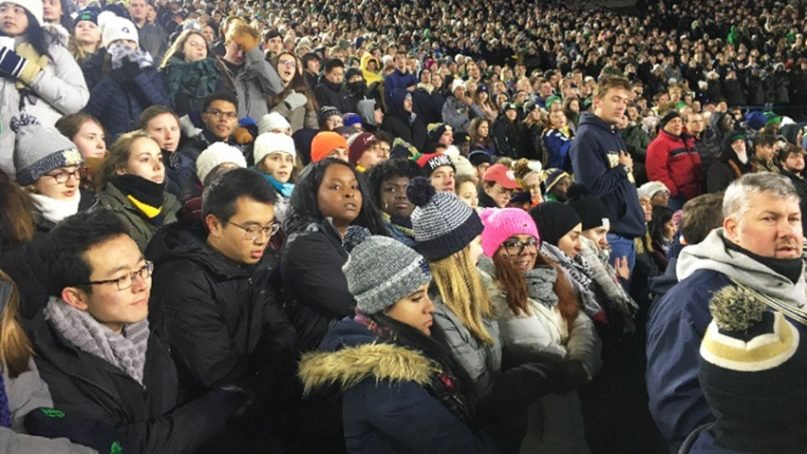 Notre Dame students link arms and kneel during the national anthem to protest racial injustice before the university's football game on Nov. 10, 2018, in South Bend, Ind. Photo courtesy of Madeleine Thompson