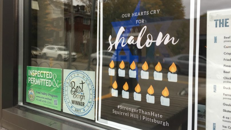 """Stores in Squirrel Hill display signs of solidarity Nov. 2, 2018, in the wake of the Tree of Life shooting. The posters say: """"Our hearts cry for Shalom."""" RNS photo by Yonat Shimron"""