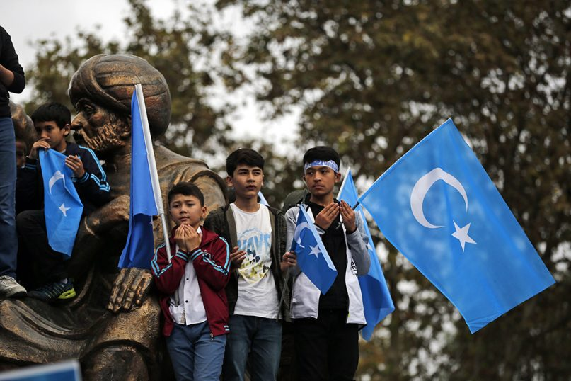 Boys from the Uighur community living in Turkey take a break to pray during a rally in Istanbul on Nov. 6, 2018. The group, carrying flags of what ethnic Uighurs call 'East Turkestan,' protested against what they allege is oppression by the Chinese government to Muslim Uighurs in China's far-western Xinjiang Province. (AP Photo/Lefteris Pitarakis)