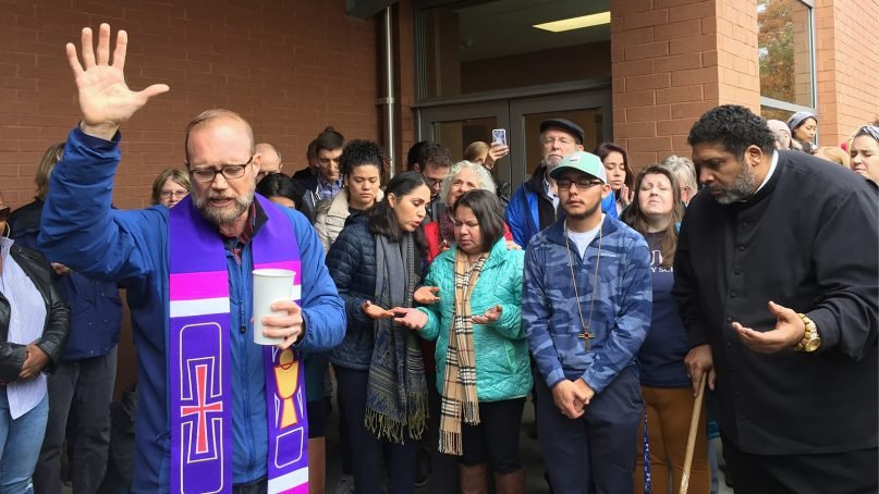 Cleve May, left, pastor of CityWell Church, flanked by Samuel Oliver's wife and son with the Rev. William Barber II, right, at a protest outside the Wake County Detention Center in Raleigh, N.C., on Nov 26, 2018. RNS photo by Yonat Shimron