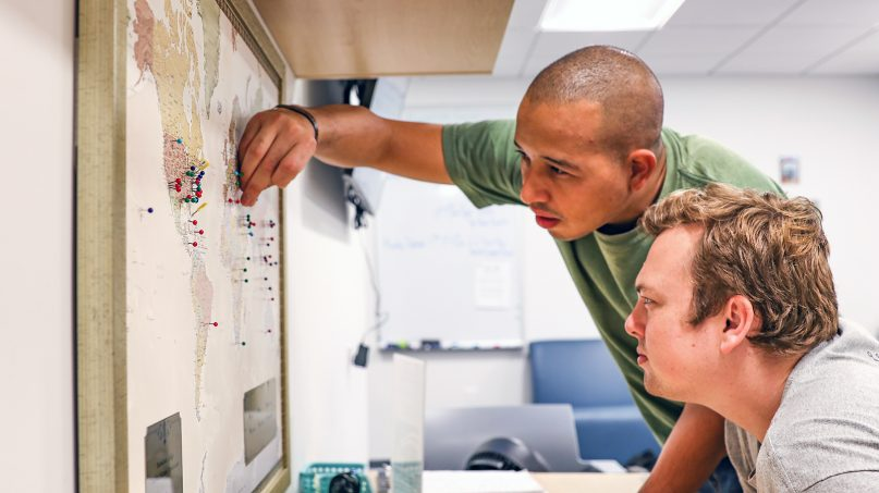 Student veterans add pins to a deployment map at the Manhattan College Student Veterans Organization office on Sept. 11, 2018, in the Bronx, N.Y. Photo courtesy of Manhattan College