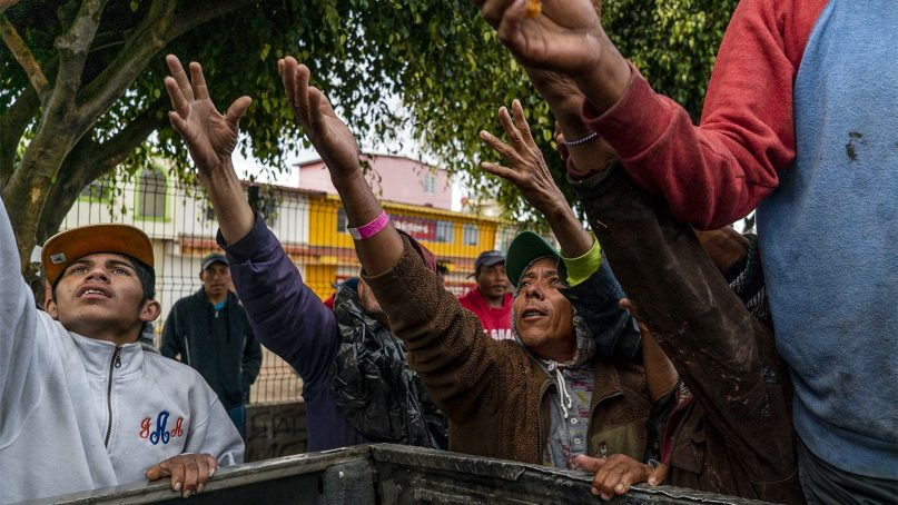 Honduran migrants ask for food from a mobile aid group in Tijuana, Mexico, on Nov. 29, 2018. RNS photo by Jair Cabrera Torres