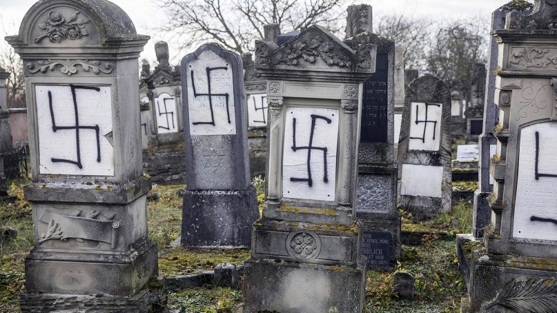 Jewish tombstones are seen desecrated with swastikas in the Herrlisheim Jewish cemetery, north of Strasbourg, in eastern France, on Dec. 13, 2018. Dozens of tombs were defaced. (AP Photo/Jean-Francois Badias)