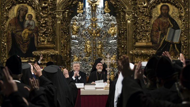 Ukrainian President Petro Poroshenko, center left, attends a closed-door synod of three Ukrainian Orthodox churches to approve the charter for a unified church and to elect leadership in the St. Sophia Cathedral in Kiev, Ukraine, on Dec. 15, 2018. Poroshenko has told the crowd