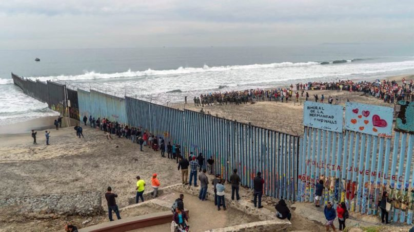 People protest against U.S. immigration policies on the American side, right, of the U.S.-Mexico border in Southern California on Dec. 10, 2018. RNS photo by Jair Cabrera Torres