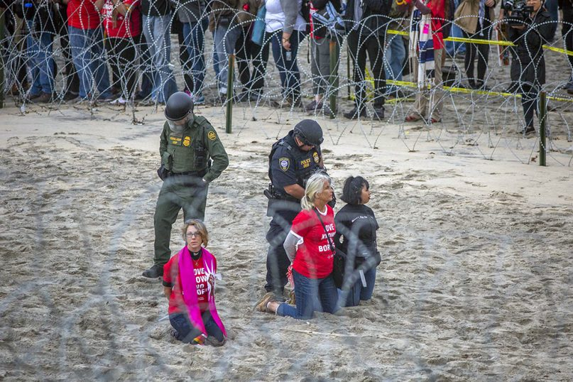 border police arrest clergy and other protesters at a rally on the american side of the us mexico border in southern california on dec 10 2018