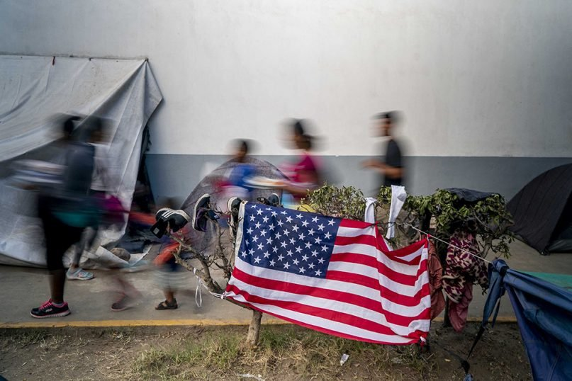 Migrants pass by the U.S. flag in Tijuana, Mexico. RNS photo by Jair Cabrera Torres