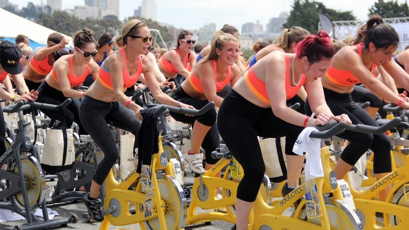 """Women participate in an outdoor SoulCycle class. SoulCycle and other""""cult"""" fitness programs are considered by some to serve as a form of church for regular participants.Photo courtesy of Creative Commons"""