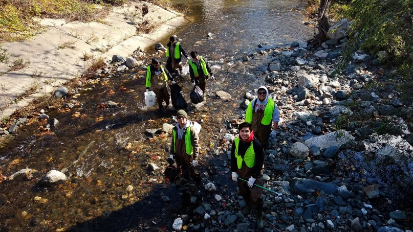 Youth from Shrine of the Sacred Heart Catholic Church remove trash from the Jones Falls stream, which runs right alongside the church property. Trash from the church's parking lot and numerous surrounding paved surfaces, roads, schools and shopping plazas empties into the stream. Photo by Bonnie Sorak/Interfaith Partners for the Chesapeake