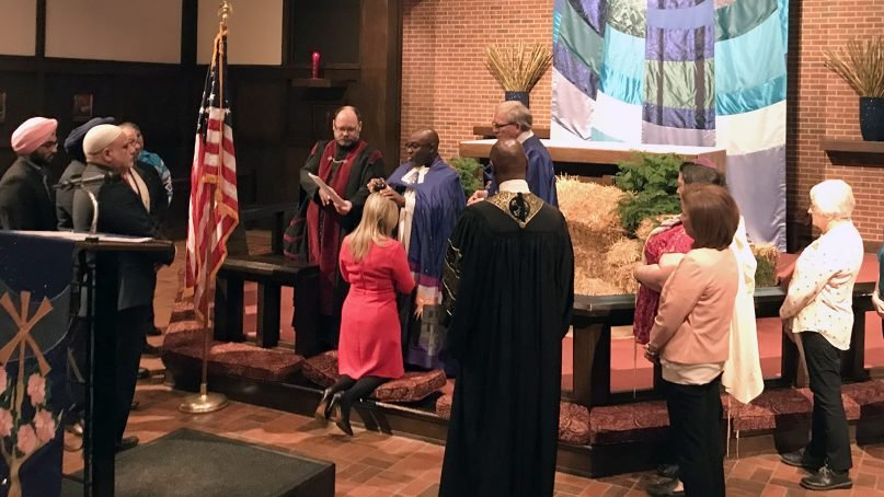 The Rev. Joseph Alsay, rector of St. Augustine of Canterbury Episcopal Church in Oklahoma City, anoints U.S. Rep.-elect Kendra Horn, D-Okla., with chrism, a consecrated oil, on Dec. 16, 2018. Representatives of various religions surround her at an interfaith prayer service at the Episcopal church. RNS photo by Bobby Ross Jr.