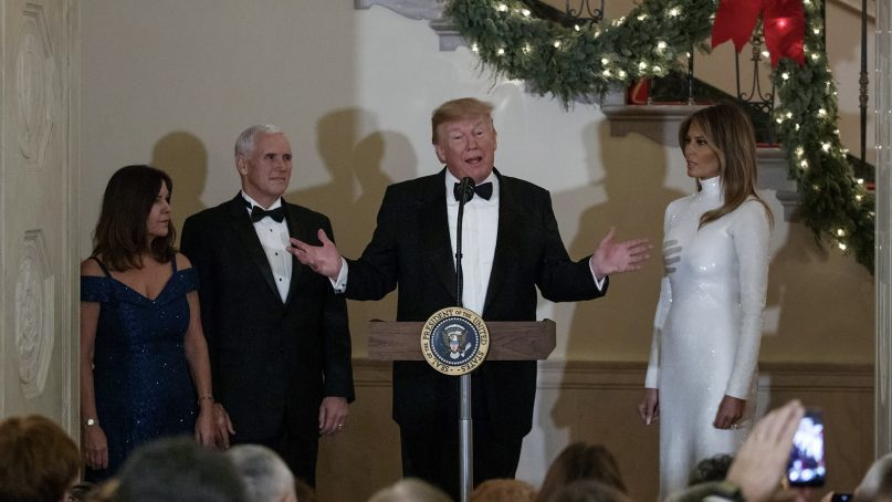 President Trump, joined by Karen Pence, from left, Vice President Mike Pence and first lady Melania Trump, speaks during the Congressional Ball in the grand foyer of the White House on Dec. 15, 2018. (AP Photo/Carolyn Kaster)