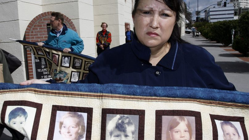 Esther Miller, who says she is a victim of child sexual abuse, holds a quilt with photos of people who say they were abused as children by priests, in front of St. Joseph's Cathedral in San Diego during a protest against the Roman Catholic Diocese of San Diego's filing of bankruptcy Wednesday, Feb. 28, 2007. The diocese filed for Chapter 11 bankruptcy protection a few hours before it was to go to trial Wednesday in the first of more than 140 lawsuits accusing priests of sexual abuse. (AP Photo/Denis Poroy)