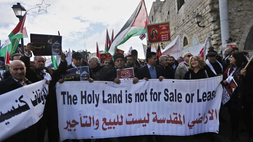 Palestinian demonstrators protest against the visit of Greek Orthodox Patriarch of Jerusalem Theophilos III to the Church of the Nativity, in the West Bank city of Bethlehem, on Jan. 6, 2018. Palestinians have been demanding his resignation for allegedly selling church land to Israelis in sweetheart deals. (AP Photo/Majdi Mohammed)