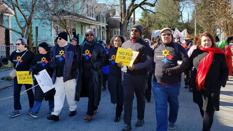 People from Pittsburgh's New Light Congregation and Rodman Street Missionary Baptist Church join members of Mother Emanuel AME Church and the Charleston Jewish Federation to march in Charleston's Martin Luther King Jr. Day Parade on Jan. 21, 2019.  Marchers included Beth Kissileff, second from left, with her husband Rabbi Jonathan Perlman, third, the Rev. Eric Manning of Mother Emanuel AME Church, fourth from left, with his wife Andretta Manning and son Eric Manning II. Also marching are director of the Charleston Jewish Federation Judy Corsaro, right, and Rabbi Adam Rosenbaum, second from right, of Synagogue Emanu-El in Charleston. Photo by Brandon Fish/Charleston Jewish Federation