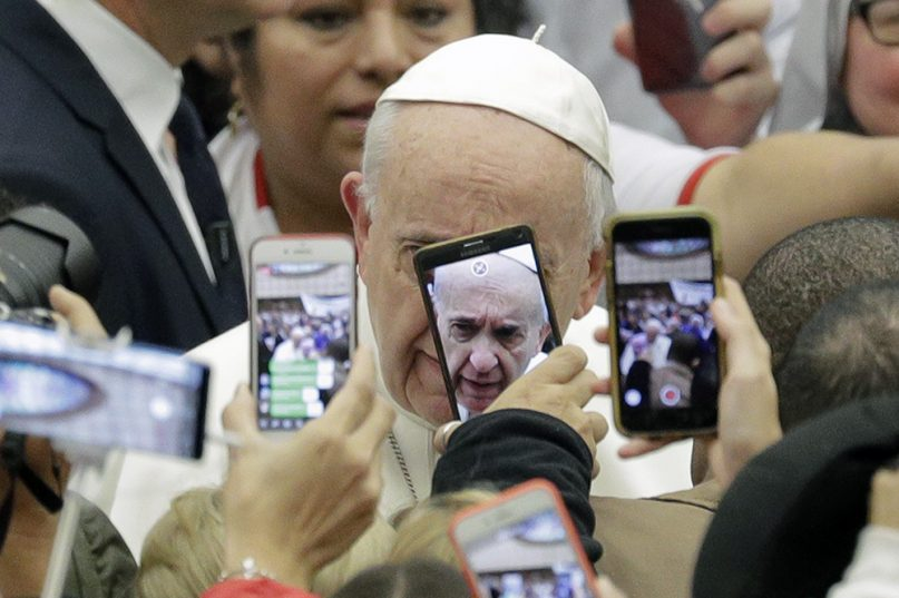 Pope Francis is framed by cellphones as he arrives for his weekly general audience in the Pope Paul VI Hall at the Vatican on Jan. 9, 2019. (AP Photo/Andrew Medichini)