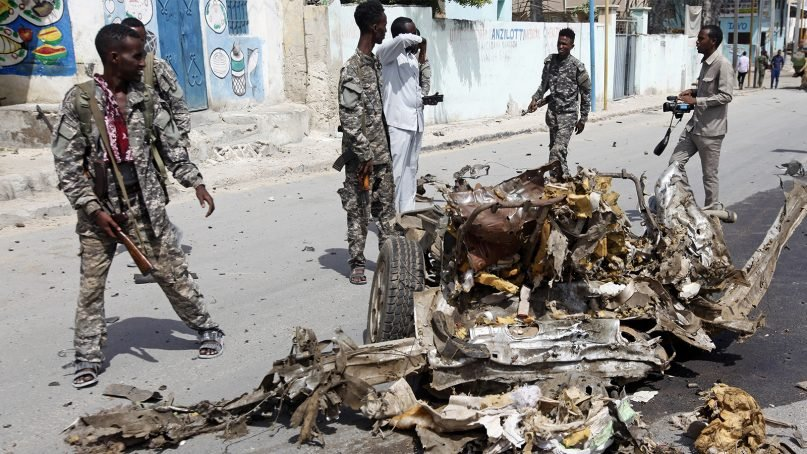 Soldiers walk around the wreckage of a car bomb near the Somali presidential palace in Mogadishu, Somalia, on July 14, 2018. It and many similar attacks in the country and region are orchestrated by the  al-Shabab terrorist group. (AP Photo/Farah Abdi Warsameh)