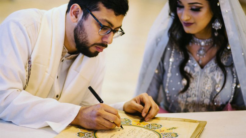 A couple signs their marriage contract. Photo courtesy of Nikahnama
