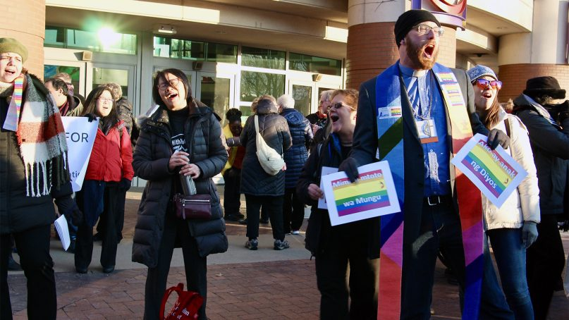 The Rev. Austin Adkinson, right, and members of the Queer Clergy Caucus sing and greet attendees on the first day of deliberations at the special session of the United Methodist Church General Conference in St. Louis on Feb. 24, 2019. RNS photo by Emily McFarlan Miller