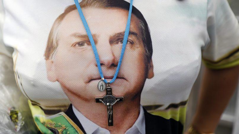 A supporter of Brazilian President Jair Bolsonaro wears a crucifix necklace over a shirt with Bolsonaro's likeness prior to his inauguration, in Brasilia, Brazil, on Jan. 1, 2019. (AP Photo/Silvia Izquierdo)