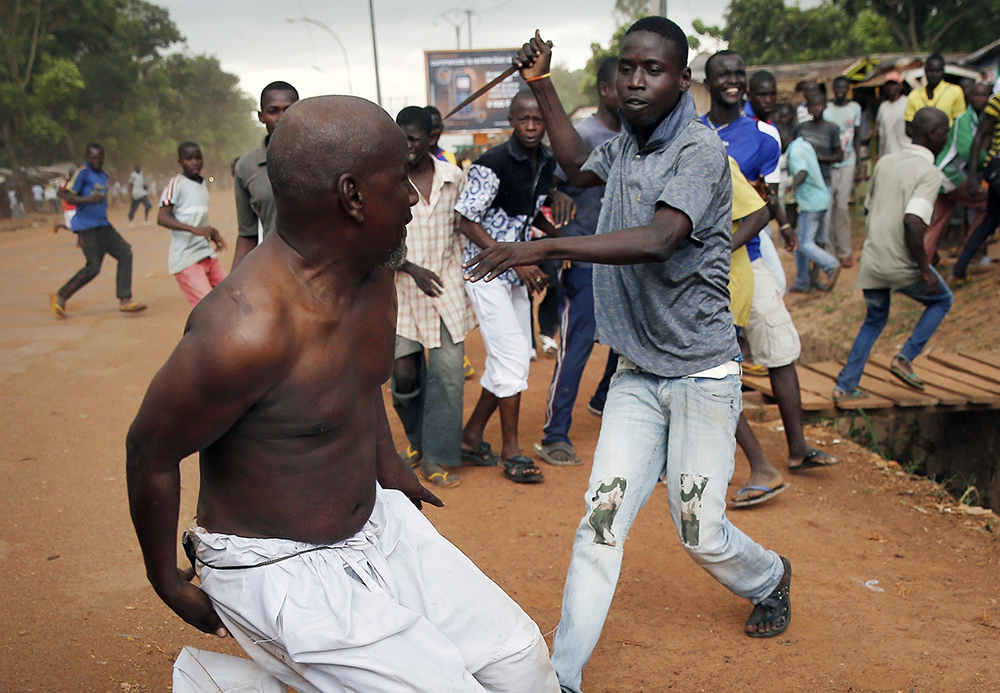 In this Dec. 9, 2013, file photo, a Christian man, right, chases a suspected Muslim Seleka officer in civilian clothes with a knife near the airport in Bangui, Central African Republic. Central African Republic and 14 rebel groups signed a peace deal on Wednesday, Feb. 6, 2019 even as some expressed alarm about the possible suspension of prosecutions after five years of bloody conflict. (AP Photo/Jerome Delay)
