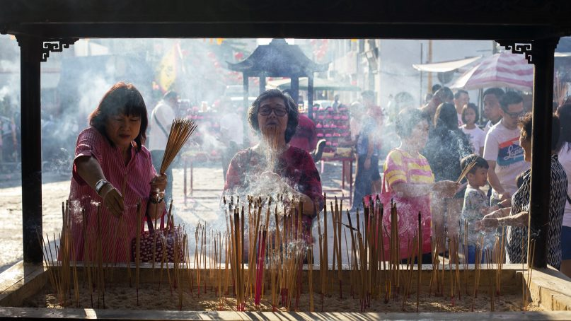 Women burn joss sticks at the Goddess of Mercy temple in Penang, Malaysia, on Feb. 6, 2019. The old Taoist temple is one of the busiest temples in Penang, with large numbers of worshippers praying there throughout the 15 days of the Spring Festival. RNS photo by Alexandra Radu