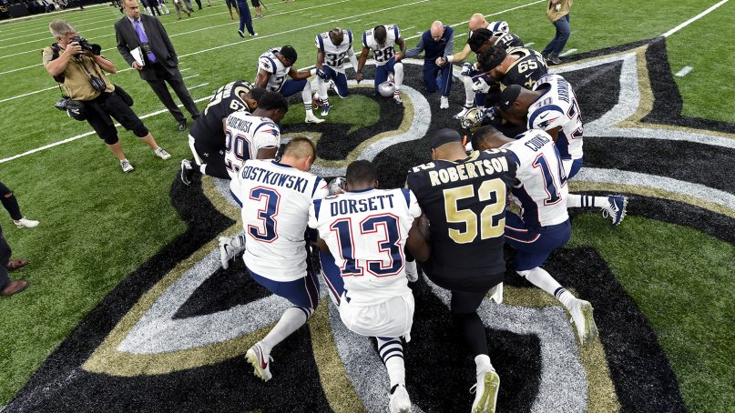 New Orleans Saints and New England Patriots players form a prayer circle after an NFL football game in New Orleans on Sept. 17, 2017. (AP Photo/Bill Feig)
