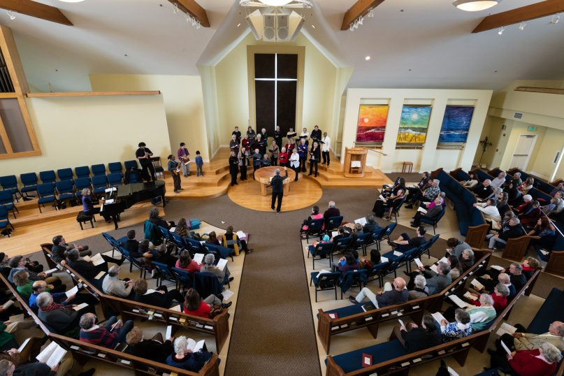 Members of First Congregational Church of Bellingham celebrate the grand opening of the Ground Floor with prayers and song during a worship service on Feb. 10, 2019. The day center for homeless youth sits directly below the church's sanctuary. (Photo by Gregg Brekke)