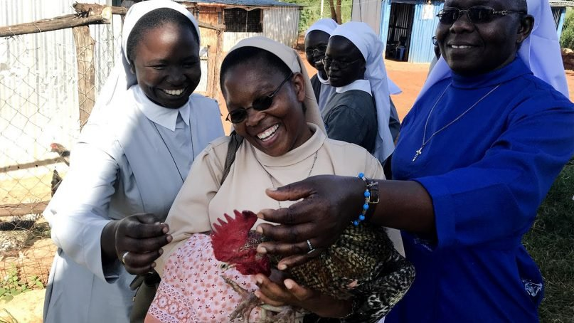 Sisters in Kenya handle chickens while learning about social enterprise opportunities at a poultry farm. Photo courtesy of Santa Clara University