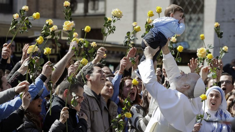 John Malkovich lifts a baby during the filming of